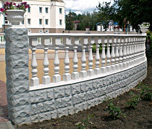 Белый бетонный забор с ажурными столбами