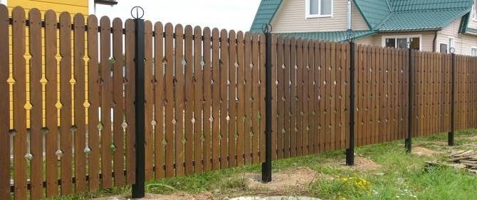 Забор из досок с металлическими столбами