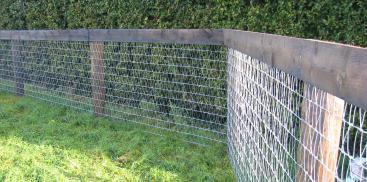 Забор из сетки рабицы с деревянными столбами